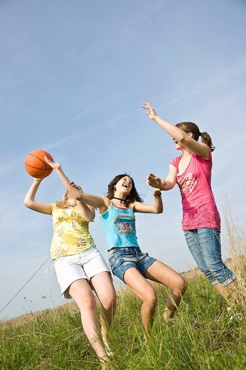 Three girls playing with a basketball on a meadow : Stock Photo