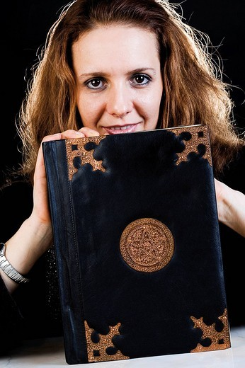 Fortune teller holding a book of spells : Stock Photo