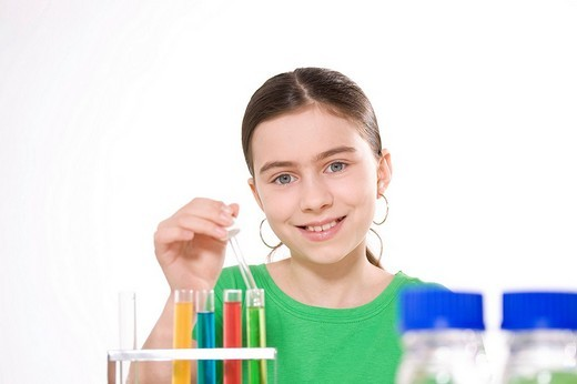 Girl working on an experiment with test tubes : Stock Photo