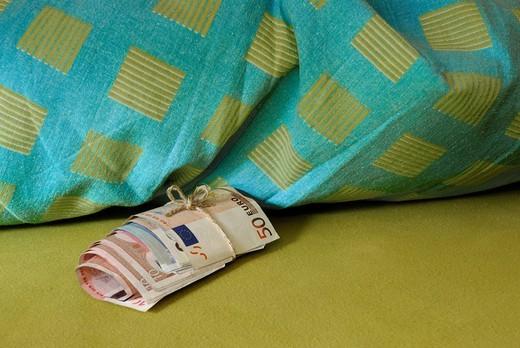 Savings kept under a pillow, roll of cash : Stock Photo