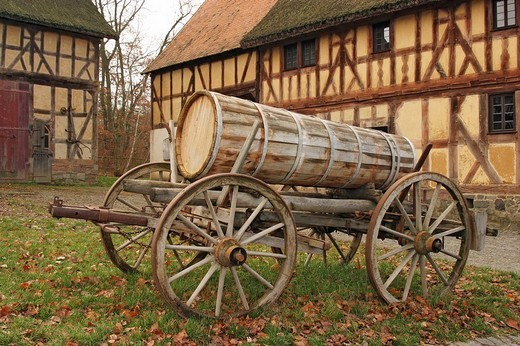 Ancient wooden cart with wooden barrel in front of framework building, open-air museum Hessenpark, Hesse, Germany : Stock Photo