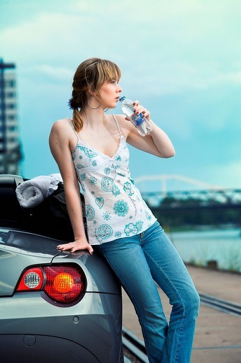 Young woman with a convertible, at a harbour : Stock Photo