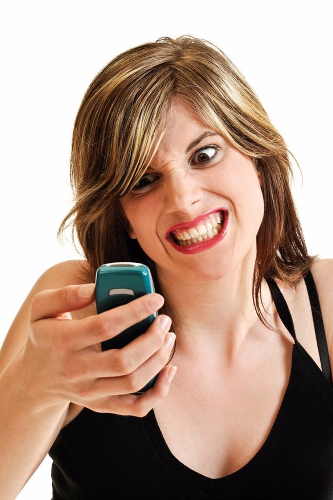 Young woman with an angry expression holding a cellphone in her hand : Stock Photo