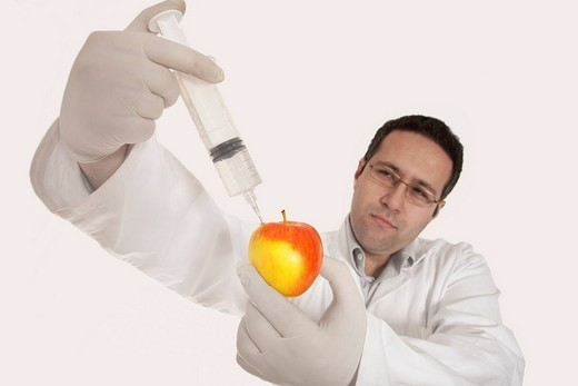 Chemist injecting a substance into an apple : Stock Photo