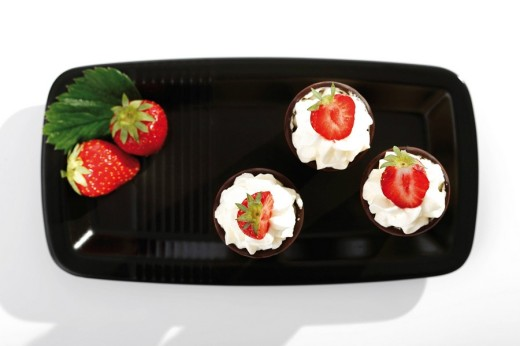 Three wafer cones with cream and strawberries on a black tray : Stock Photo