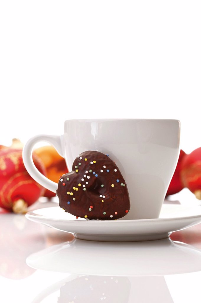 Coffee cup and a small heart-shaped gingerbread cookie, Christmas balls at back : Stock Photo