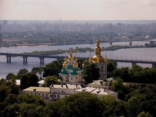 Ukraine Kiev the belower monstery of cave Kyjevo Pecers´ka Lavra view to the belltower of far caves and godmothers birth church in background bridge over river Dnepr monastery surrounded by green trees 2004 : Stock Photo