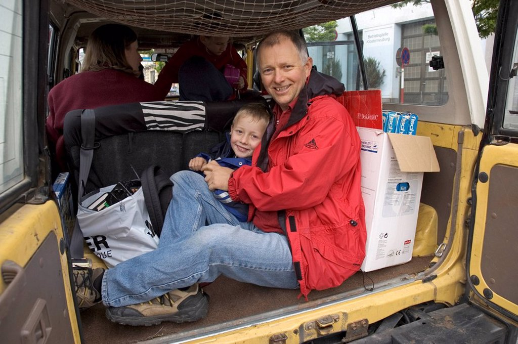 Father and six year old son in the back of a Toyota Landcruser 4 wheel drive in Klosterneuburg near Vienna Austria : Stock Photo