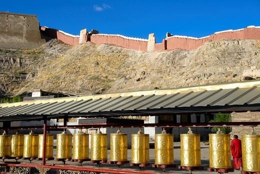 Long row of golden prayer wheels Pelkor Chöde Monastery Gyantse Tibet China : Stock Photo