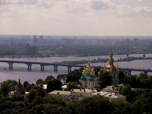 Ukraine Kiev the belower monstery of cave Kyjevo Pecers´ka Lavra view to the belltower of far caves and church of god mothers birth in background bridge over river Dnepr golden domes in green forrest 2004 : Stock Photo
