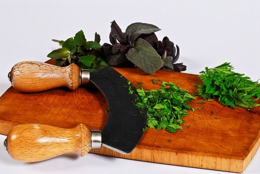 Herbs, Calamintha, Cicely, Salvia get cut with a mincing knife : Stock Photo