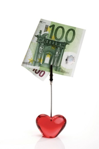 Stock Photo: 1848R-320262 Red glass heart holding a 100-Euro bill: love for sale