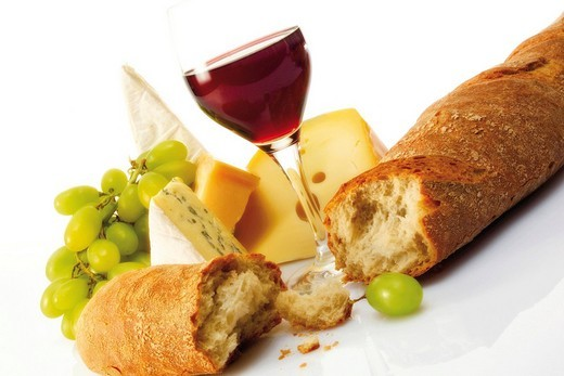 Baguette with a glass of red wine and various types of cheese : Stock Photo