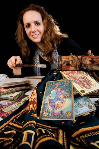 Fortune teller holding a wand over a magic box, a cloth decorated with the signs of the zodiac and tarot cards : Stock Photo