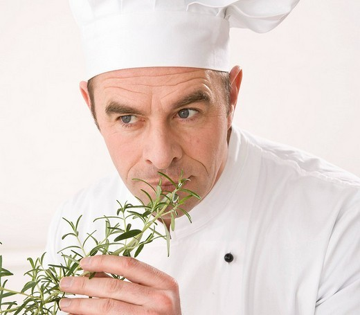 Stock Photo: 1848R-322726 Cook smelling a branch of rosemary