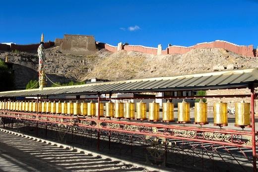 Stock Photo: 1848R-323679 Long row of golden prayer wheels Pelkor Chöde Monastery Gyantse Tibet China