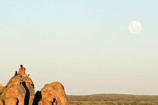 Namibian man sitting beside young tame Yellow Baboon Papio cynocephalus on a rock formation in late afternoon light watching the full moon rise over the grassland plains, Namibia, Africa : Stock Photo