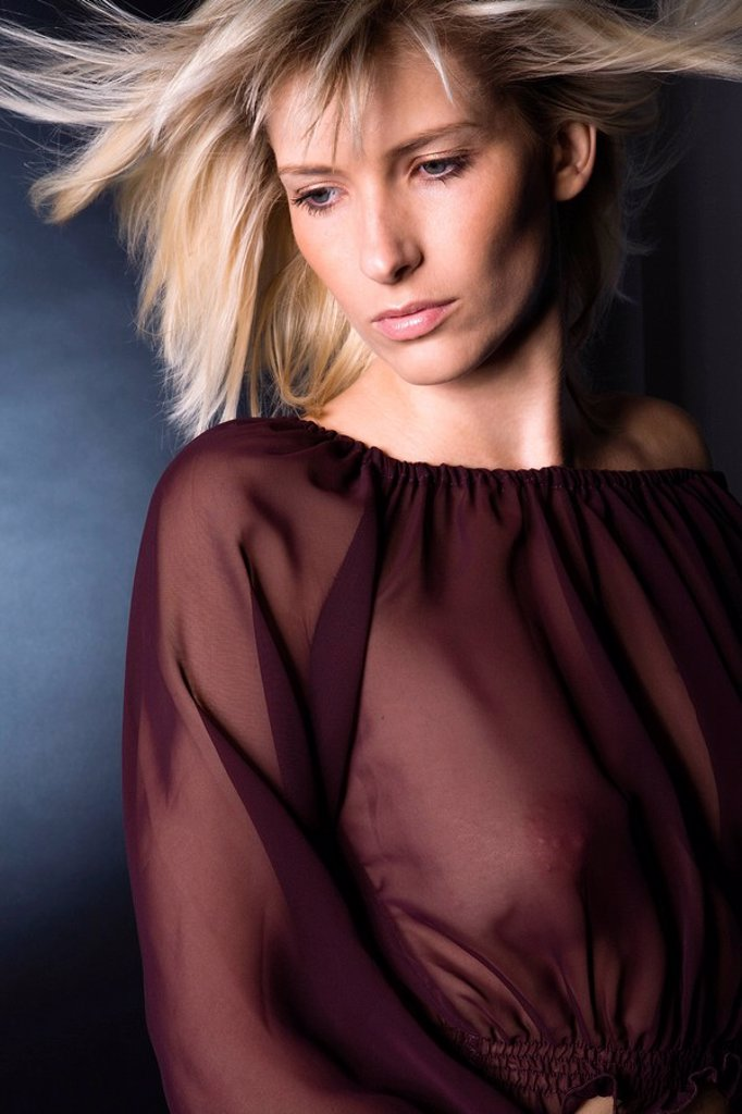 Portrait of a young, blond girl with a transparent blouse : Stock Photo