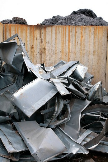 Piled up aluminium parts in front of a concrete wall in the scrapyard : Stock Photo
