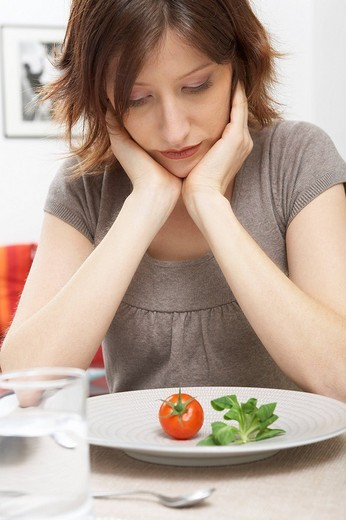 Stock Photo: 1848R-325554 Young woman with a single tomato and piece of lettuce on her plate