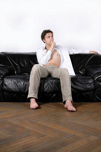 Young man on a leather sofa : Stock Photo