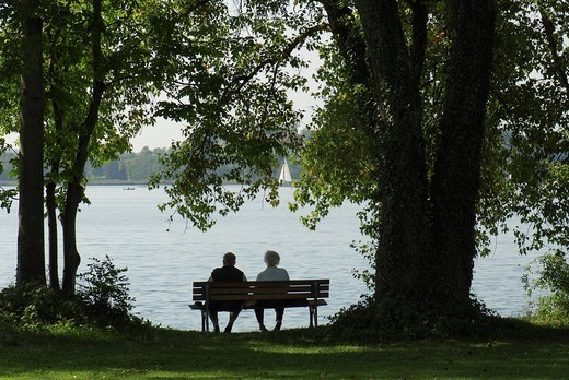 Old married couple sitting on a park bench at lake Chiemsee, Upper Bavaria, Bavaria, Germany : Stock Photo