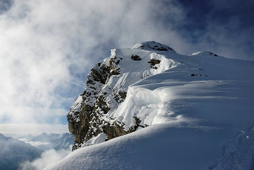 Stock Photo: 1848R-328504 Ice fog circulates rocky peak loaded with heavy snow drifts Zillertal alps Austria