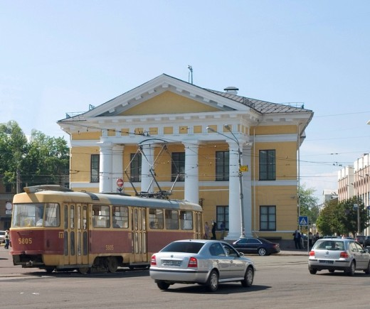 Ukraine Kiev district Podil Kontraktova Place oldest place of town view to the historical building of contrakts and the tram traffic with cars and walking people blue sky 2004 : Stock Photo