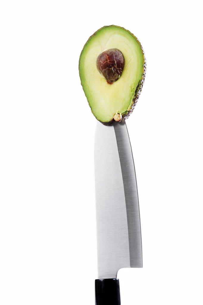 Avocado half on a knife : Stock Photo