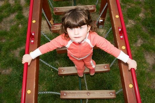 Little girl, 3 years old, on rocking bridge : Stock Photo