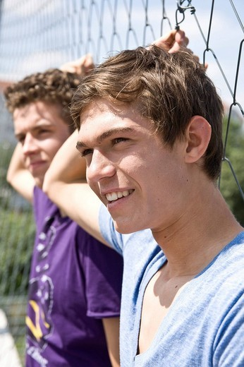 Stock Photo: 1848R-331146 Two guys leaning against a fence, cool, looking into the distance