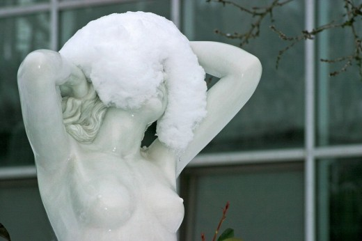 Statue of a woman half covered with snow : Stock Photo