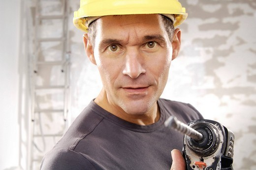 Workman wearing a hard hat, holding a drill : Stock Photo