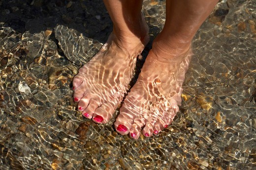 Woman´s feet in mountain stream : Stock Photo