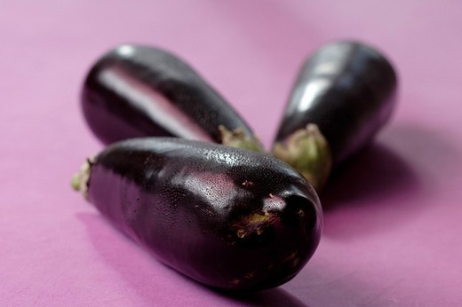 Stock Photo: 1848R-338950 Three aubergines against lilac subsurface