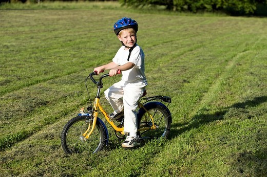 Stock Photo: 1848R-339222 Young boy, 4 years old, wearing helmet and riding a bike in a meadow