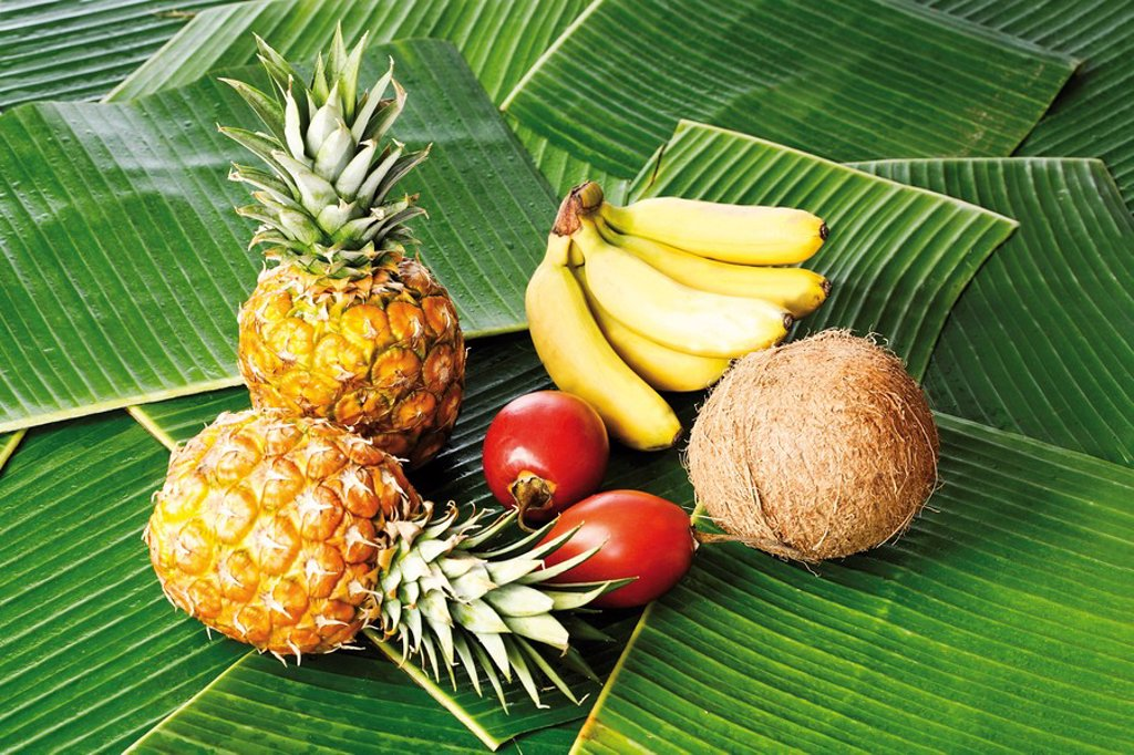 Tropical fruits on bed of banana leaves, baby pineapples, Ananas comusus, tamarillos, Solanum betaceum, coconuts Cocos nucifera and baby bananas Musaceae : Stock Photo