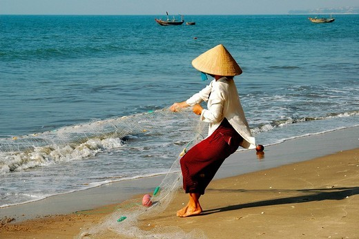 Fisher woman hauling in the fishing net, Mui Ne, Viet Nam : Stock Photo