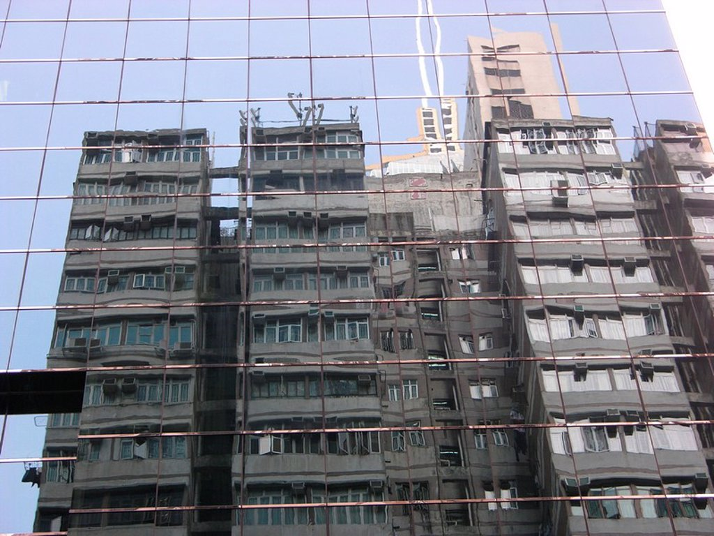 Reflection of an old high-rise building facade in some new one from glass and steel - Hong Kong, China, Asia : Stock Photo