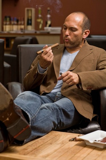Young man smoking a cigar : Stock Photo