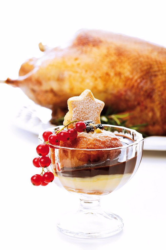 Baked apple with chocolate sauce and custard, out-of-focus roast christmas goose in the back : Stock Photo