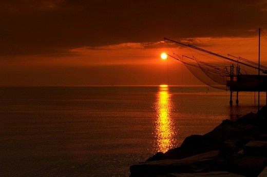 Rocks and fishing nets on the coast at sunrise, red coloured sky and sea : Stock Photo