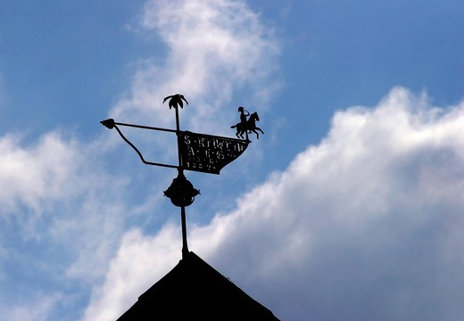 Stock Photo: 1848R-344267 Silhouette of a weather vane on rooftop against blue sky with cloud
