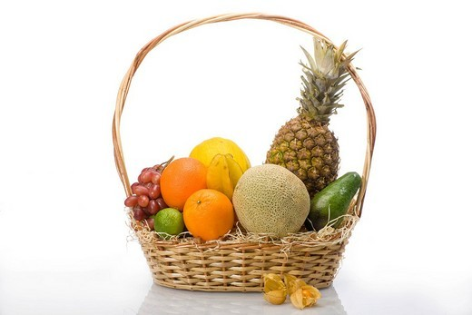 Exotic fruit in a basket, pineapple, melons, grapes, oranges, lime, physalis, avocado : Stock Photo