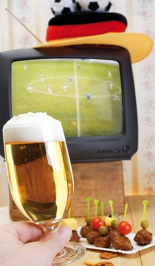 Stock Photo: 1848R-345294 Retro football broadcast - TV broadcast of a game, football hat, tray of skewered meatballs and hand holding a glass of beer