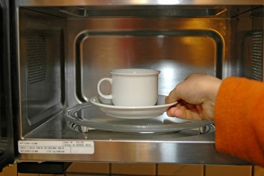 Stock Photo: 1848R-345938 Coffee is heated up in microwave