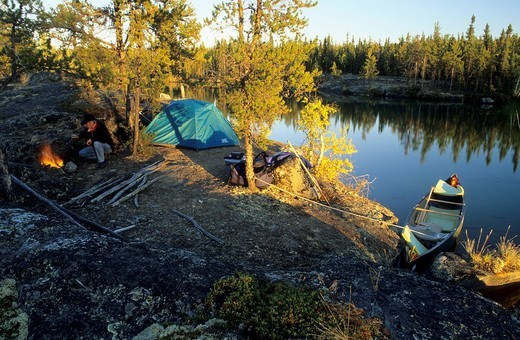 Man at campfire on a lakeshore, Northwest Territories, Canada : Stock Photo