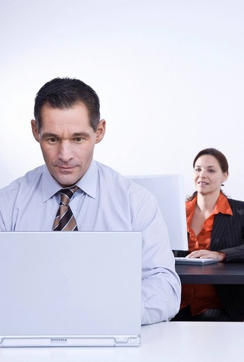 Stock Photo: 1848R-346589 Businessman and businesswoman working on their laptops in an office