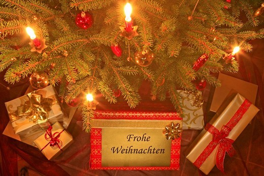 Decorated christmas tree with candles and porcelain ornaments, presents under the tree : Stock Photo