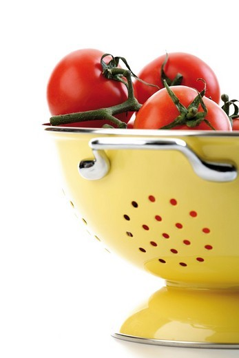 Stock Photo: 1848R-348346 Truss of tomatoes in a yellow kitchen sieve